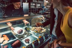 Experienced chef choosing raw seafood from the freezer for two customers royalty free stock images