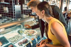 Experienced chef choosing raw seafood from the freezer for two customers stock image