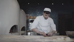 An experienced chef in white uniform prepares a delicious kebab. Cook puts the stuffing in the dough. An experienced chef in white uniform prepares a delicious stock video