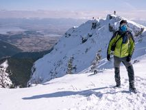 Experienced climber at the top of winter mountains stock image