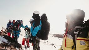 Experienced climbers stopped for a rest on top of the snow-capped mountains, relax and translate breath stock video footage