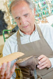 Experienced cobbler gluing sole in place. Experienced cobbler gluing a sole in place royalty free stock images