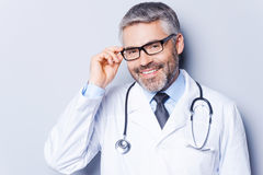 Experienced and confident doctor. Cheerful mature doctor adjusting his eyeglasses and smiling while standing against grey background stock photography