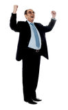 Experienced corporate man sharing success. Corporate man standing with arms up against white background Royalty Free Stock Photo