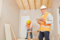 Experienced craftsman with carpenter. At construction site stock photography