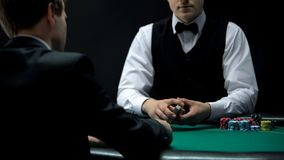 Experienced croupier holding cards deck ready to deal, chance to win in poker. Stock photo stock image