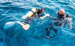 Experienced diver instructor teaches a beginner diver to dive in Egypt royalty free stock photography