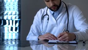 Experienced doctor examining x-ray and writing diagnosis in medical form, health royalty free stock photo