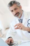 Experienced doctor giving pills to patient. Mature doctor in hospital giving pills to patient royalty free stock images