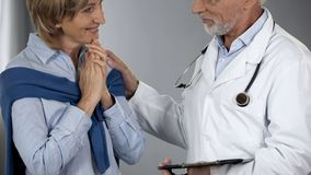 Experienced doctor informing lady about positive treatment results, good news royalty free stock images