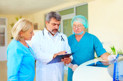 Experienced doctor and medical staff consulting about health record in hospital Stock Images