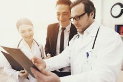 Experienced doctor with nurse shows results of analyzes to smiling businessman in office. stock photo
