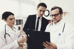 Experienced doctor with nurse and troubled businessman looks at results of medical examination. royalty free stock images