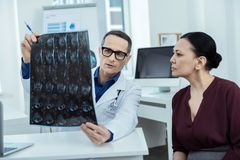 Experienced doctor showing a brain scan stock image