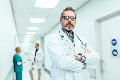 Experienced doctor standing in hospital corridor stock photography