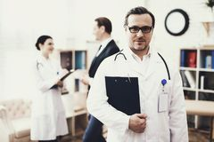Experienced doctor with stethoscope is standing with folder of documents. Convalescence concept. Blurred businessman talks with nurse in background Stock Image