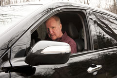 Experienced Driver. Experienced male driver looking at rearview mirror through SUV window royalty free stock photo