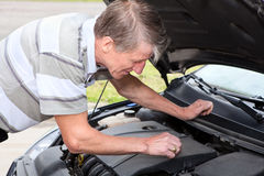 Experienced driver examining car engine. Experienced Caucasian driver check up a oil level in car motor Stock Photography