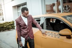 Experienced driving instructor standing near nice bright orange car. Instructor near car. Experienced professional driving instructor standing near nice bright stock photography