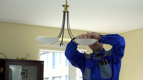 Experienced electrician changing light bulbs at client home. Worker man in blue uniform with tools in pocket stock footage