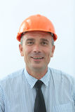 Experienced engineer in orange helmet and a positive attitude. Closeup of the face of the engineer who smiles and looks forward, on a white background. the photo stock photography