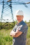 Experienced engineer with white hard hat under the power lines. Engineer work at an electrical substation stock image