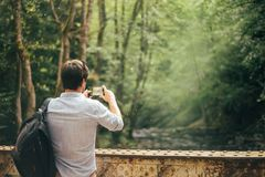 Experienced fashionable dark-haired tourist, man takes a photo on his new phone, advertising and announcement, the. Delightful nature of Georgia, bright green royalty free stock photos