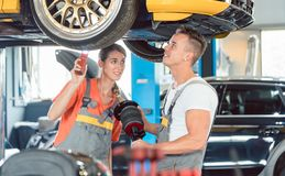 Experienced female auto mechanic with colleague a Royalty Free Stock Photos