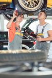 Experienced female auto mechanic with colleague at repair shop. Experienced female auto mechanic checking tires before installing together with her colleague a stock photography
