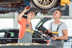 Experienced female auto mechanic installing a new air suspension system Stock Photo