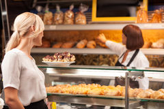 Experienced female baker is selling baked products Stock Photography