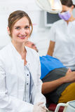 Experienced female Dentist in her surgery. Female Dentist in her surgery looking at the viewer, in the background her assistant is giving a male patient a stock photos