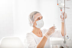 Experienced female doctor putting drip stock photos