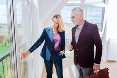 Experienced female estate agent showing window view her rich client. Window view. Experienced female estate agent showing window view her rich client wearing stock images