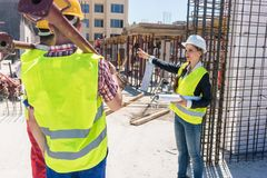 Experienced female foreman coordinating and guiding workers. By showing them the right direction during work on the construction site of a contemporary building royalty free stock image