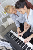 Experienced female master piano hand helps student stock images
