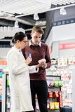 Experienced pharmacist checking the indications of a medicine. Experienced female pharmacist checking the indications and contraindications of a new medicine stock images