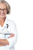 Experienced female physician. Cropped image. Cropped image of cheerful lady doctor posing confidently stock photos
