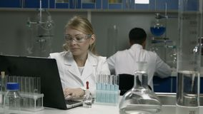 Female scientist conducting an experiment in lab stock video footage