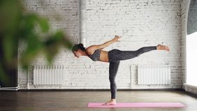 Experienced yoga teacher is practicing standing half forward bends and variations of warrior poses in light spacious. Experienced female yoga teacher is stock video footage