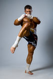 An experienced fighter kickboxer with a raised foot. full height Stock Photo