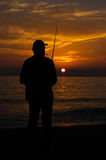 Experienced fisherman silhouette smokes cigarette against the setting sun Royalty Free Stock Photography