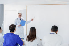Experienced general practitioner explaining information to students stock images