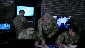 Experienced general beside from soldiers, in dispatch room, Military personnel working stock footage