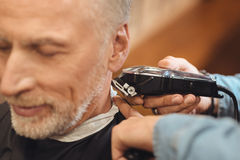 Experienced hairdresser making hairdo to aged client in salon Royalty Free Stock Photography