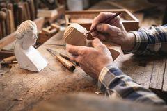Artisan sketching the outlines of a wooden sculpture royalty free stock photos