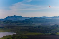 Experienced hang-glider hovering above hilly landscape royalty free stock images