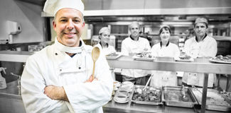 Experienced head chef posing proudly in a modern kitchen. With his team in the background stock images