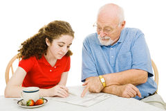 Experienced Help. Teen girl filling out absentee ballot gets help from her grandfather.  Isolated on white Royalty Free Stock Photos