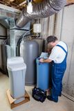 Experienced home installer fixing a water softener. Experienced home installer fixing issues encountered on a new water softener tank that he is installing using Royalty Free Stock Photo